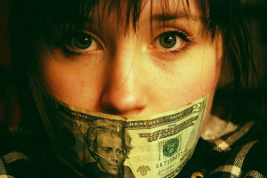 20 dollar bill covering woman's mouth representing the value of customer-driven research