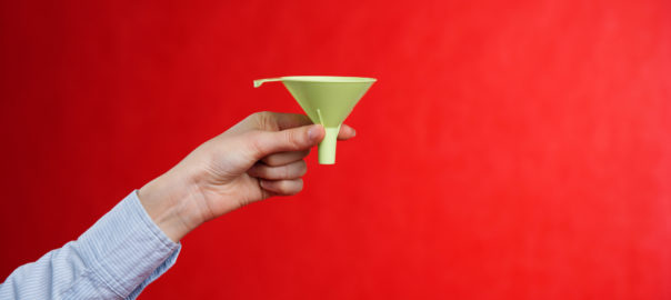 Female hand holding a green funnel on a red background. Sifting the truth. Be able to analyze.